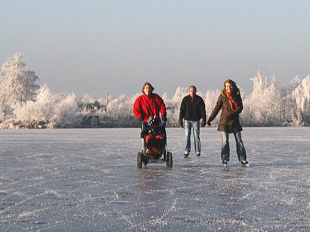 Ice-skating family with a baby in buggy